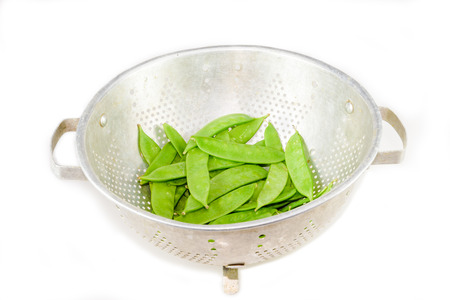 a colander: Clean Snow peas in the colander on the white background Stock Photo