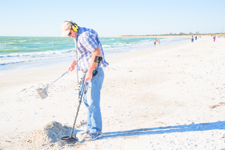 metal detector: A man on  the beach working on metal detector