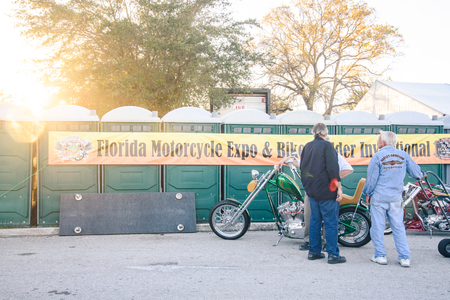 Clearwater,FL-FEB 19,2017;Undentified men talk to each other in front of the banner and motorcycles ,on the Florida Motorcycle Expo and Bike Builder Invitational at 49th St.N.,Clearwater FL-Feb19th,2017