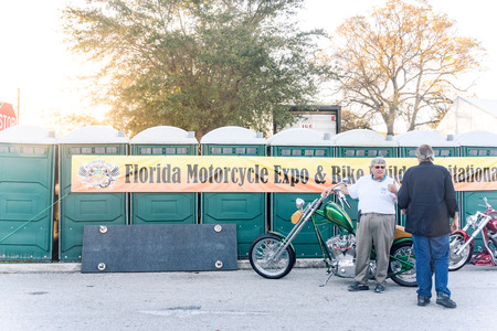 Clearwater,FL-FEB 19,2017;Undentified men talk to each other in front of the banner and motorcycles ,on the Florida Motorcycle Expo and Bike Builder Invitational at 49th St.N.,Clearwater FL-Feb19th,2017 Redakční