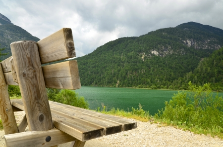 Bench on teh bank of mountain lake photo