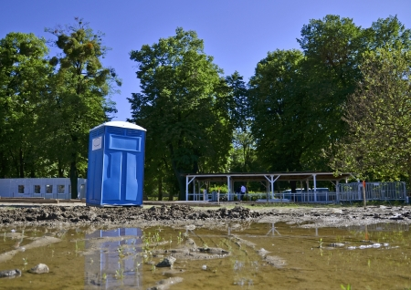 self contained: Blue Portable Toilet in the middle of muddy park