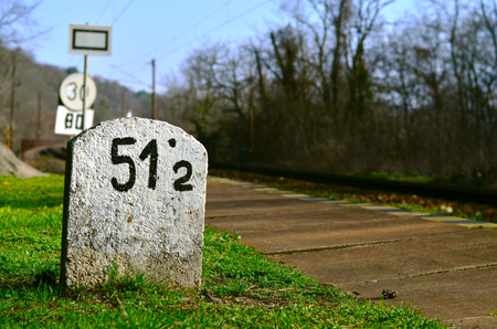 An old milestone in the grass on the side of an electrified railroad with, trolley lines, signalling device, several railway signs and bare trees in the background