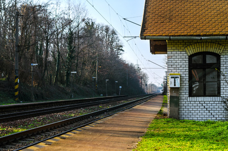 signalling: An old abandoned railway train station building next to the long straight electrified railroad with stoplights, trolley lines and several signalling devices  Stock Photo