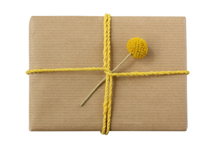 beautifully wrapped: Beautifully wrapped gift - eco-friendly kraft paper decorated with yellow twine and flower - isolated on white