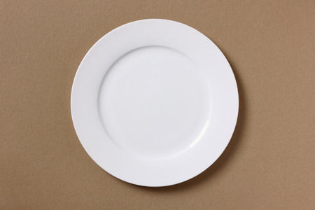 paper plates: White empty plate on brown kraft-paper background - taken from above Stock Photo