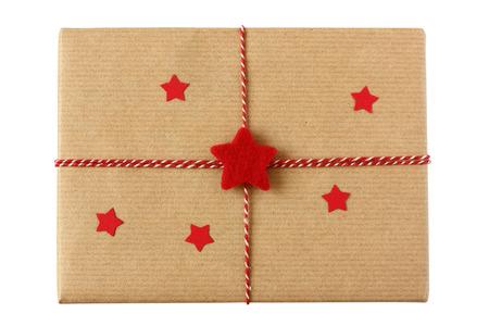 papier naturel: Colis de No�l envelopp�s dans du papier naturel et d�cor� avec des �toiles rouges et ficelle - isol� sur blanc