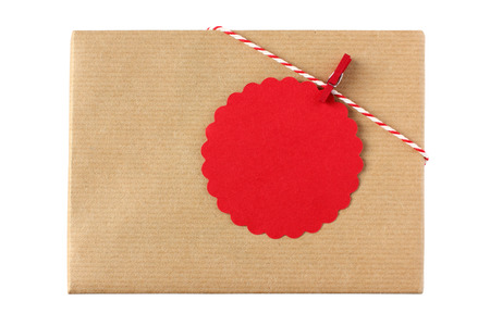 christmas tag: Christmas present decorated with red twine and red gift tag with copy space - isolated on white background