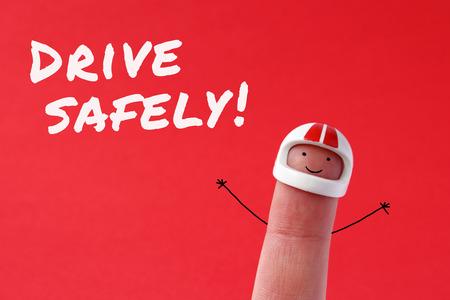 dedo: Conduzca con seguridad - figura divertida dedo llevaba un casco con Conduce con cuidado el texto escrito en fondo rojo