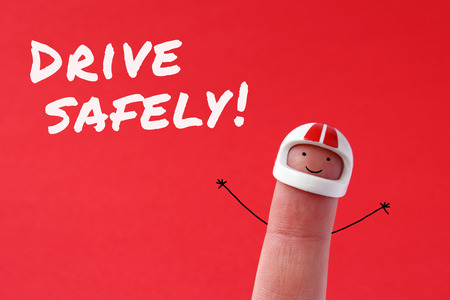 safely: Drive safely - funny finger figure wearing a helmet with Drive safely text written on red background