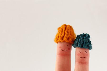 invierno: Divertido los dedos en pareja sonriente con las mejillas rojas vistiendo sombreros de lana de punto Foto de archivo