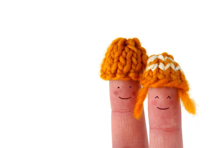 Cute smiling couple with yellow hand-knitted wool hats - isolated on white