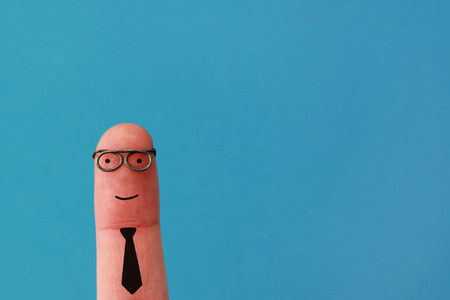 dedo: Feliz el hombre de negocios sonriente sobre fondo azul - la gente divertida del dedo Foto de archivo