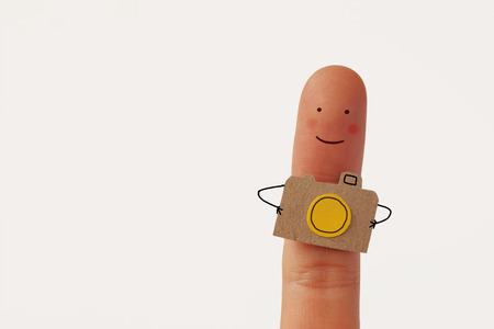 Funny finger tourist holding a camera and smiling