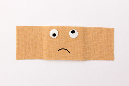 Get well soon - Band-aid with comic face expression looking sick or feeling bad Stock Photo