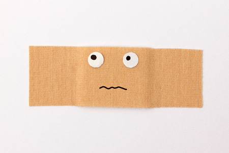 Plaster with comic face expression looking worried photo