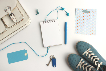 Top view of bag accessories collection content in blue color theme with bag, shoes, pen, blank notepad, paper tag, headphone and keys