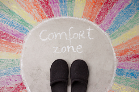 Leaving your comfort zone motivational concept - empty shoes left standing in comfort zone drawing Stock Photo