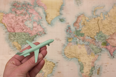 wanderlust: Wanderlust concept with hand holding airplane and blurred map background Stock Photo