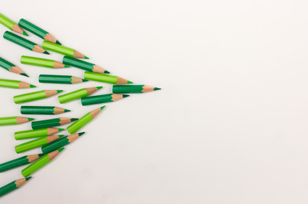 lay forward: Crowd of green pens pointing to the right - team workshop, strategy, success, leadership concept with space for copy text Stock Photo