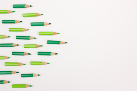 lying forward: Many green pens forming an arrow to the right with space for copy text - useful image for business success, strategy, workshop background