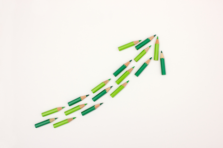 lay forward: Many green pens forming an arrow pointing upwards - useful image to visualize success, growth, innovation with copy space available Stock Photo