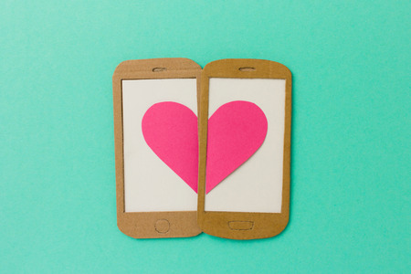 copy text: Two mobile phone screens combining a pink heart - paper illustration image concept for online dating, flirting, chatting with space available for copy text Stock Photo