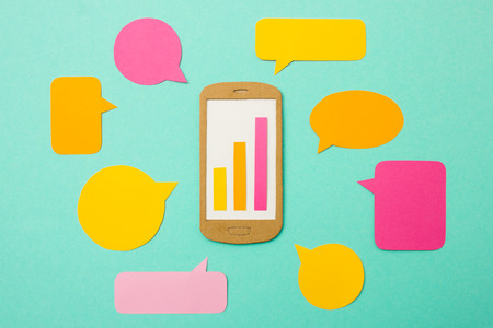 handmade paper: Handmade paper model of smartphone with growth chart and speech bubbles - useful image for mobile marketing, mobile commerce or advertising Stock Photo