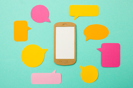 handmade paper: Handmade paper model of smartphone with many speech bubbles - useful image for mobile marketing, customer support, advertising for chat applications Stock Photo