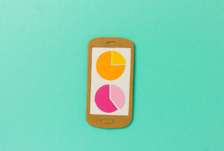 the reporting: Handmade paper model of smartphone with pie charts - image concept for analytical apps, accounting, financial reporting, customer research