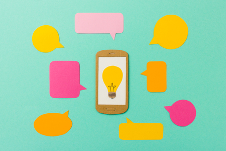 phone symbol: Smart phone with light bulb symbol and talk bubbles - concept for e-elearning, online classes, mobile marketing, apps and communication