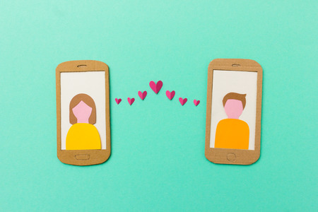 dating: Online dating and mobile flirting concept - man and woman profile on smartphones connected with flying paper hearts