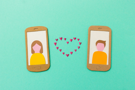 internet dating: Internet love - Online dating concept with girl and boy falling in love via smartphone