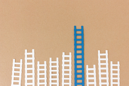 compared: Ladders concept - many paper ladders with one ladder leading much further up compared to the rest Stock Photo