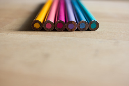 Colored pencils on wooden desk - education template background with space for your text