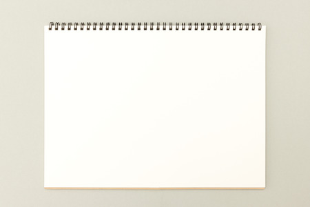 Open sketchbook with blank white page on neutral background - great template for your drawing, hand lettering or design work Stock Photo