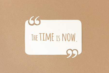 encouragement: The time is now - motivational quote on paper Stock Photo