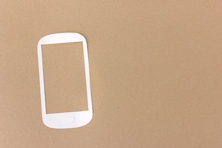 White phone cut from paper on brown background - with space to add your text