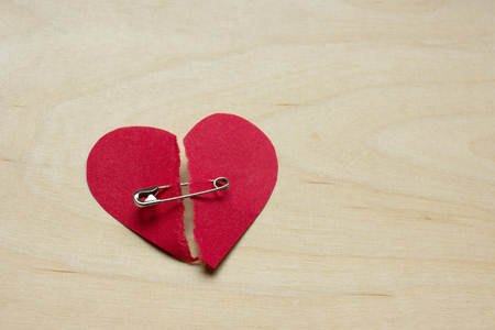 Torn red paper heart fixed together with a safety pin