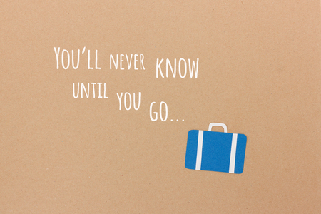 Youll never know until you go... - motivational quote with suitcase illustration on brown paper Stock Photo