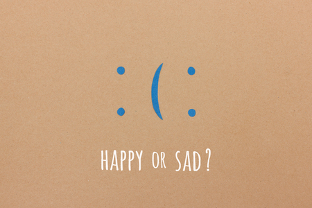 Happy or sad? You decide - paper illustration with smiley or sad emoticon depending on your point of view Stock Photo