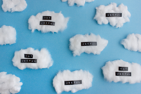 labelling: Meditation - labelling thoughts as useful and not useful  - many white cotton clouds with labels on blue background Stock Photo