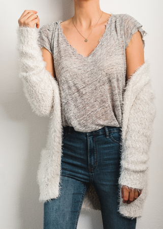 Young woman dressed gray t-shirt and fluffy knitted white cardigan. Imagens