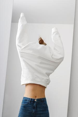Mujer vestida con jeans de cintura alta con suéter blanco delante del espejo.