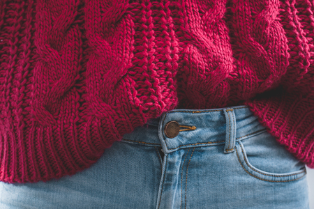 Close-up body part of woman dressed in a knitted large viscous pink sweater and blue jeans