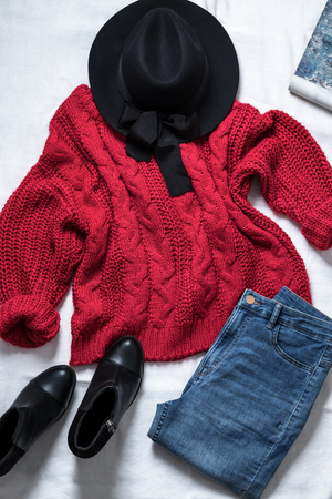 Set of casual female clothes: black woolen hat,knitted large viscous red sweater, blue skinny jeans, leather ankle boots, on white background. Top view. Imagens