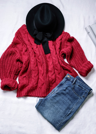 Set of casual female clothes: black woolen hat,knitted large viscous red sweater, blue skinny jeans on white background. Top view.