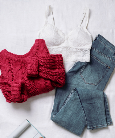 Set of casual female clothes: underwear white lace top ,knitted large viscous red sweater, blue skinny jeans on white background. Top view. Imagens
