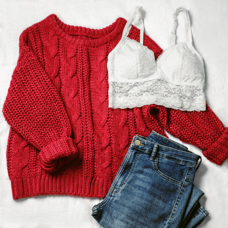 Set of casual female clothes: underwear white lace top ,knitted viscous red sweater, blue skinny jeans on white background. Top view.