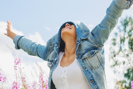 Portrait of happy girl hiding face under denim jacket walking outside. Blue sky background.